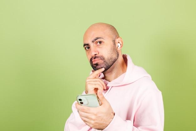 孤立したピンクのパーカーの若いハゲ白人男性、電話を保持する思慮深いあごを保持