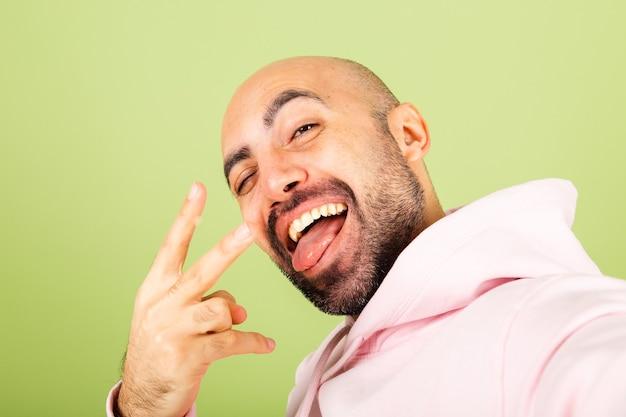 ピンクのパーカーで孤立した、ポジティブで陽気な若いハゲの白人男性は、写真のセルフィーを撮ります