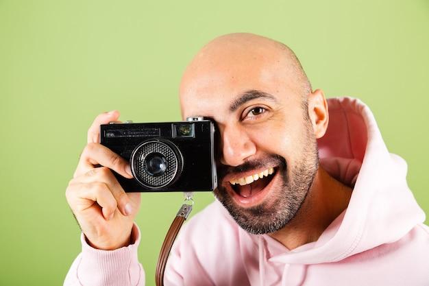 ピンクのパーカーで隔離された、ポジティブなヒップスターホールドカメラの若いハゲ白人男性
