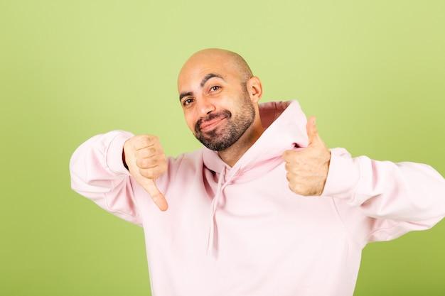 ピンクのパーカーを着た若いハゲ白人男性が孤立し、ポジティブな1つの親指を1つ下に