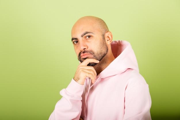 ピンクのパーカーを着た若いハゲ白人男性が孤立し、質問を心配し、心配し、あごに手を当てて緊張している