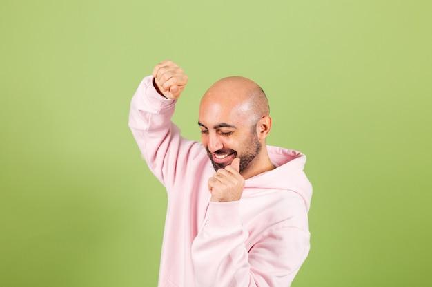 Giovane uomo caucasico calvo in felpa con cappuccio rosa isolato, felice e allegro, sorridente in movimento casuale e fiducioso ascolto di musica