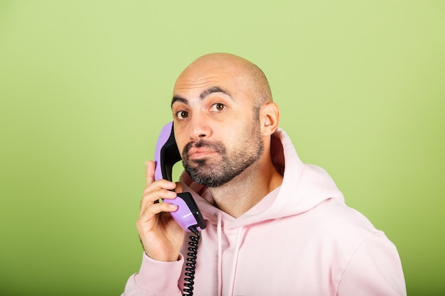 Giovane uomo caucasico calvo in felpa con cappuccio rosa isolato, tenere premuto il telefono di rete fissa con la faccia triste annoiata