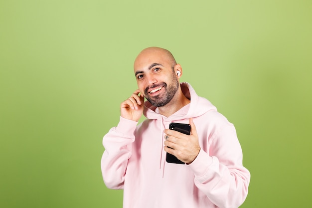 Young bald caucasian man in pink hoodie isolated, hold phone happy dancing moving in headphones enjoying with closed eyes