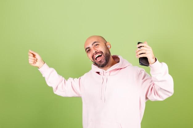 Giovane uomo caucasico calvo in felpa con cappuccio rosa isolato, tenere premuto il telefono ballando felice in movimento in cuffie godendo con gli occhi chiusi