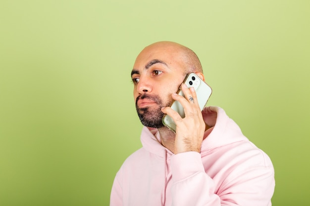 Young bald caucasian man in pink hoodie isolated, hold phone listen audio message conversation with bored sad unhappy face