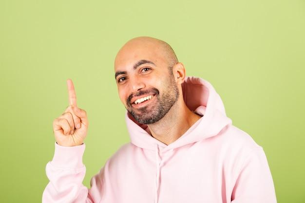 Giovane uomo caucasico calvo in felpa con cappuccio rosa isolato, guarda con sorriso puntare le dita verso l'alto