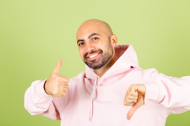 Young bald caucasian man in pink hoodie isolated, positive one thumb  up one down
