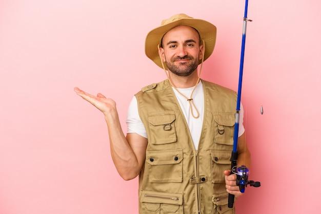 ピンクの背景に分離されたロッドを保持し、手のひらにコピースペースを示し、腰に別の手を保持している若いハゲ漁師。