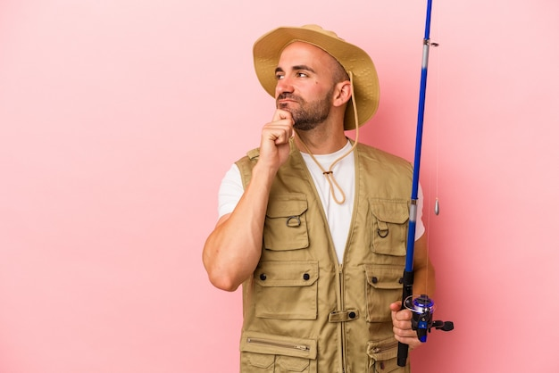 Young bald fisherman holding a rod isolated on pink background  looking sideways with doubtful and skeptical expression.