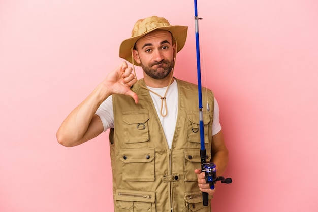 Young bald fisherman holding a rod isolated on pink background  showing a dislike gesture, thumbs down. disagreement concept.