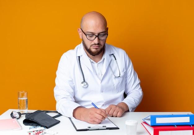 Giovane medico maschio calvo che indossa abito medico e stetoscopio in bicchieri seduto alla scrivania