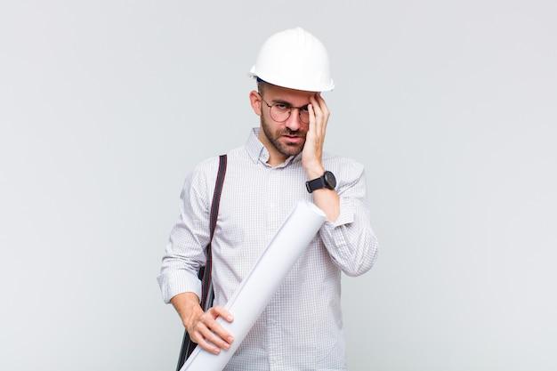 지루하고 지루하고 지루한 작업 후 지루하고 좌절하며 졸린 젊은 대머리 남자, 손으로 얼굴을 잡고