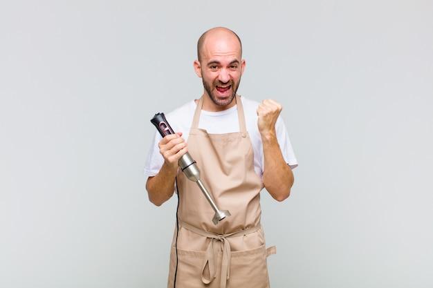 젊은 대머리 남자는 충격을 받고 흥분하고 행복하며 웃고 성공을 축하하며 와우라고 말합니다!