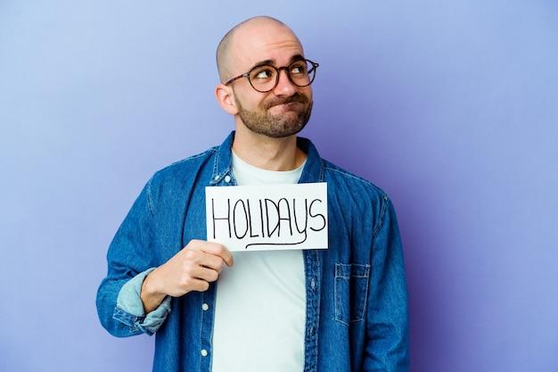 目標と目的を達成することを夢見て青い壁に分離された休日のプラカードを保持している若いハゲ男