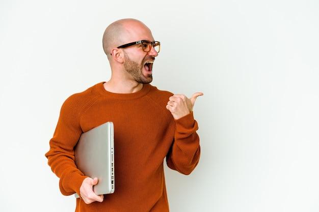 白い背景で隔離されたラップトップを持っている若いハゲ男は、親指の指を離れて、笑ってのんきなポイントを指します。