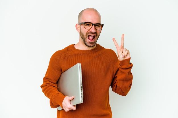 白い壁に隔離されたラップトップを持っている若いハゲ男は、指で平和のシンボルを示して楽しくてのんきです。