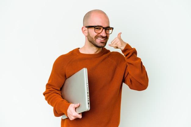 Молодой лысый мужчина, держащий ноутбук, изолированный на белой стене, показывает жест мобильного телефона пальцами