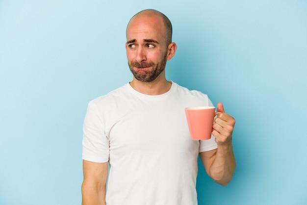 파란색 배경에 격리된 머그잔을 들고 있는 젊은 대머리 남자는 혼란스럽고 의심스럽고 확신이 서지 않습니다.