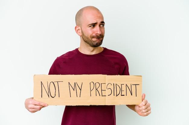 白い壁に隔離された私の大統領ではないプラカードを持っている若いハゲ男は混乱し、疑わしくて自信がない