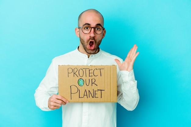私たちの惑星のプラカードの孤立した壁を保護している若いハゲ男は驚いてショックを受けました