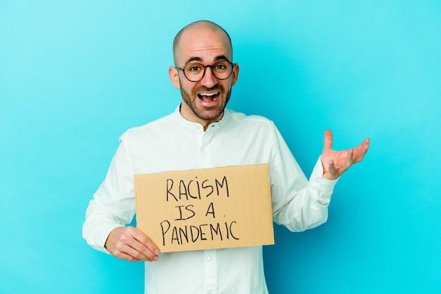 인종 차별주의를 들고 젊은 대머리 남자는 즐거운 놀라움을 받고 흥분하고 손을 올리는 흰 벽에 고립 된 유행병입니다