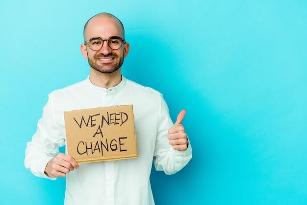 젊은 대머리 남자를 들고 우리는 미소하고 엄지 손가락을 올리는 변경 현수막 고립 된 벽이 필요합니다.