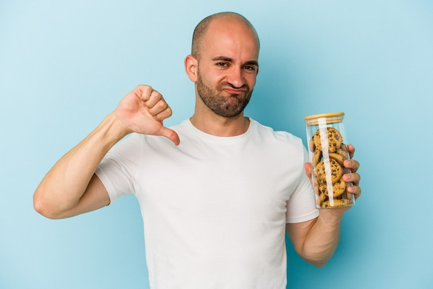 Young bald man holding cookies isolated on blue background  feels proud and self confident, example to follow.