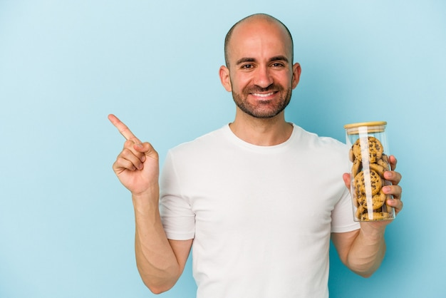 Young bald man holding cookies isolated on blue background  smiling and pointing aside, showing something at blank space.
