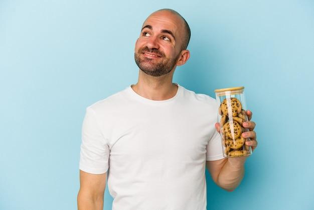 目標と目的を達成することを夢見て青い背景で隔離のクッキーを保持している若いハゲ男