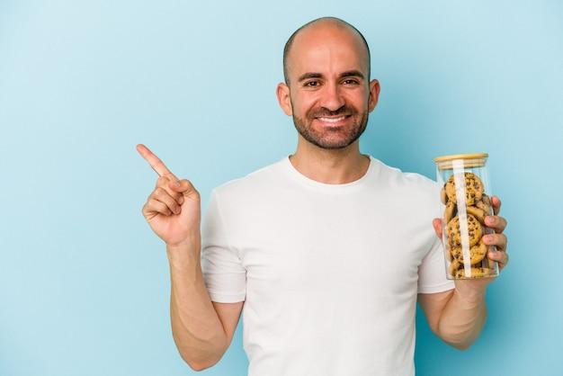 青い背景に分離されたクッキーを持っている若いハゲ男は、笑顔で脇を指して、空白のスペースで何かを示しています。