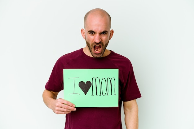 Young bald man holding a i love mom placard isolated on yellow wall screaming very angry and aggressive