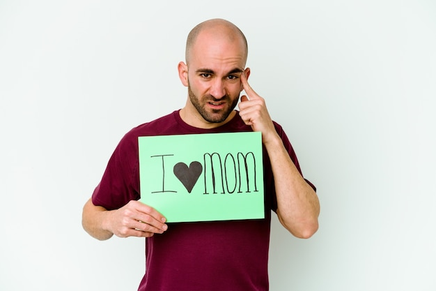 Young bald man holding a i love mom placard isolated on yellow wall showing a disappointment gesture with forefinger