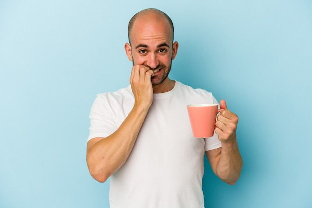 Young bald man holding a mug isolated on blue background  biting fingernails, nervous and very anxious.