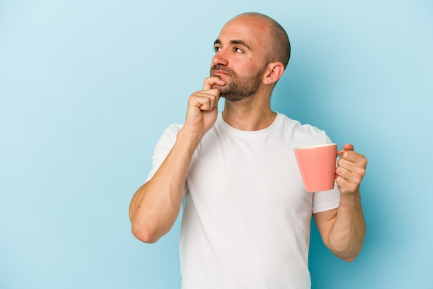 Young bald man holding a mug isolated on blue background  looking sideways with doubtful and skeptical expression.