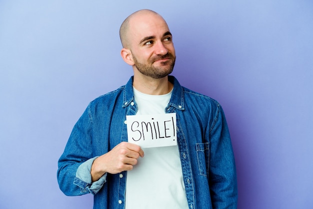 Young bald man holding a smile placard isolated wall dreaming of achieving goals and purposes
