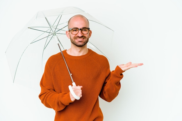Young bald man holding an umbrella isolated showing a copy space on a palm and holding another hand on waist.