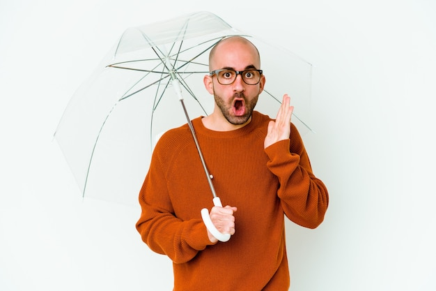 Young bald man holding an umbrella isolated surprised and shocked.