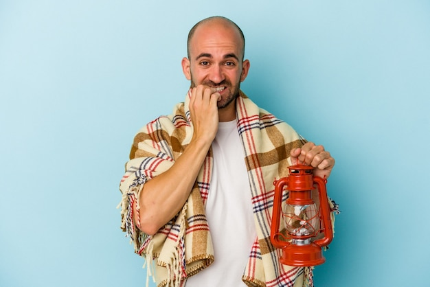 Young bald man holding vintage lantern isolated on blue background  biting fingernails, nervous and very anxious.
