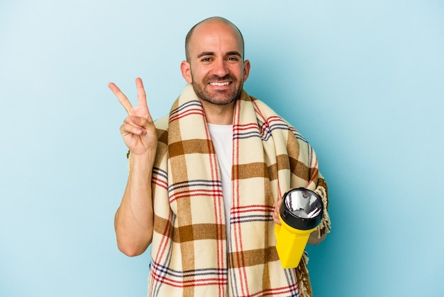 Young bald man holding vintage lantern isolated on blue background  joyful and carefree showing a peace symbol with fingers.