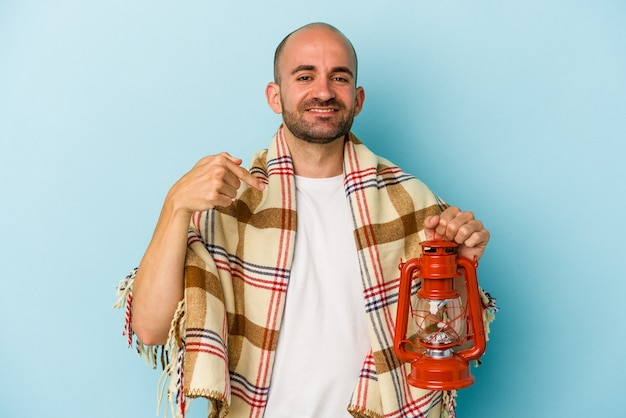 Young bald man holding vintage lantern isolated on blue background  person pointing by hand to a shirt copy space, proud and confident