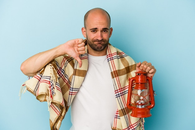 Young bald man holding vintage lantern isolated on blue background  showing a dislike gesture, thumbs down. disagreement concept.