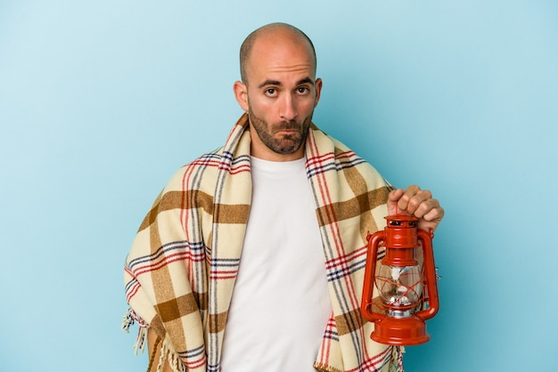 Young bald man holding vintage lantern isolated on blue background  shrugs shoulders and open eyes confused.
