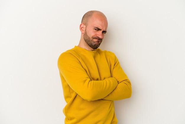 흰색 배경에 격리된 젊은 대머리 남자는 불쾌한 표정으로 얼굴을 찌푸리고 팔짱을 낀 상태로 유지합니다.