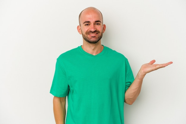 手のひらにコピースペースを示し、腰に別の手を保持している白い背景で隔離の若いハゲ男。