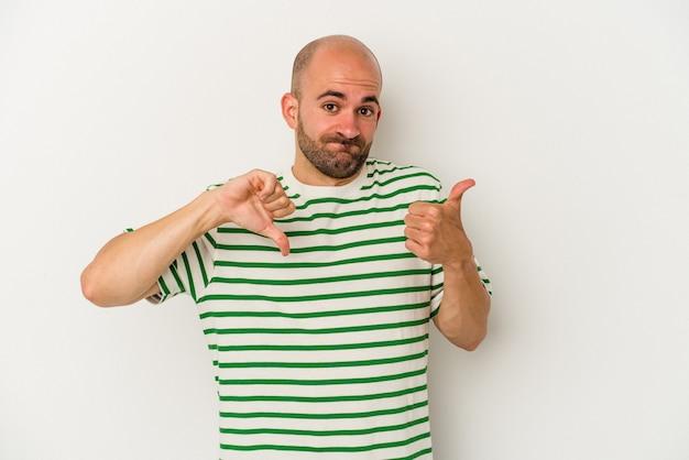 親指を上に、親指を下に示す白い背景で隔離の若いハゲ男、難しい選択の概念