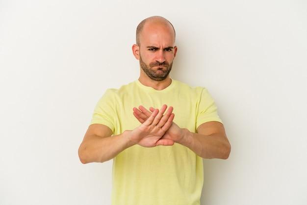 흰색 배경에 격리된 젊은 대머리 남자는 뻗은 손으로 정지 신호를 표시하고 당신을 방해합니다.
