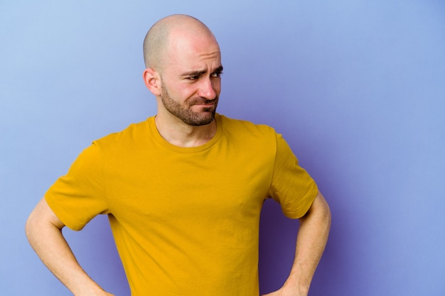 Young bald man isolated wall confused, feels doubtful and unsure