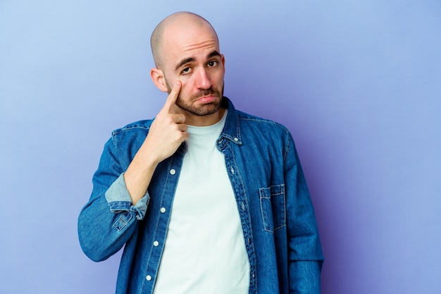 Young bald man isolated wall crying, unhappy with something, agony and confusion concept