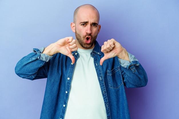 若いハゲ男は親指を下に示し、嫌いを表現する壁を分離